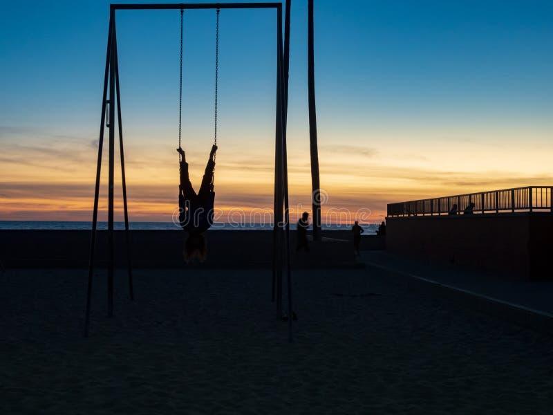 垂悬颠倒在体操圆环的人户外在海滩的黄昏天空 库存图片