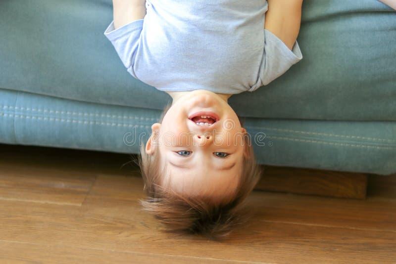 垂悬颠倒在沙发的逗人喜爱的滑稽的矮小的男婴看照相机,微笑 免版税库存照片