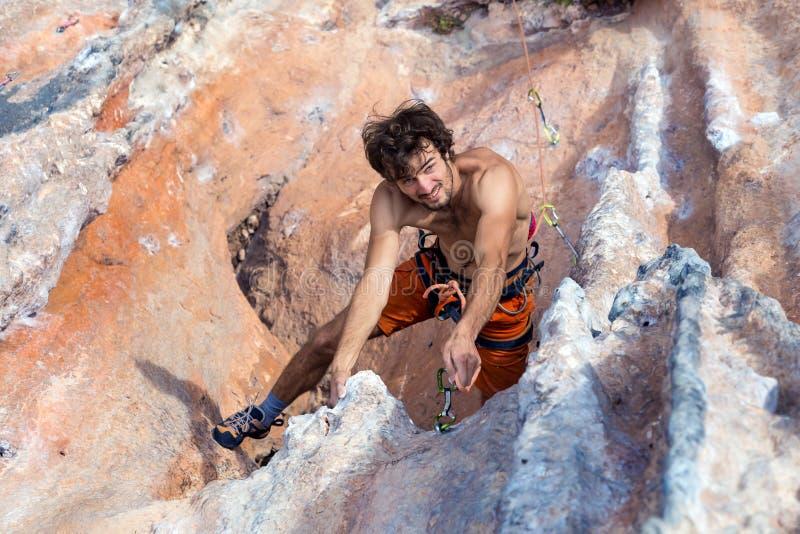 垂悬高在岩石墙壁上的微笑的登山人顶视图 免版税库存图片