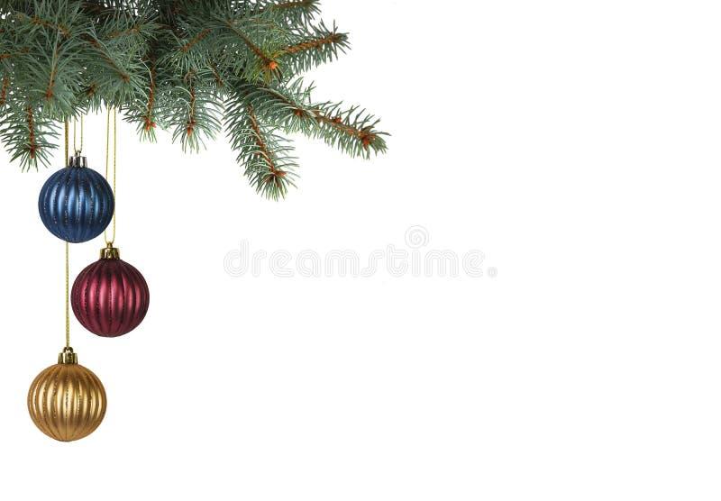 垂悬从圣诞树的明亮地色的圣诞节球 免版税库存图片