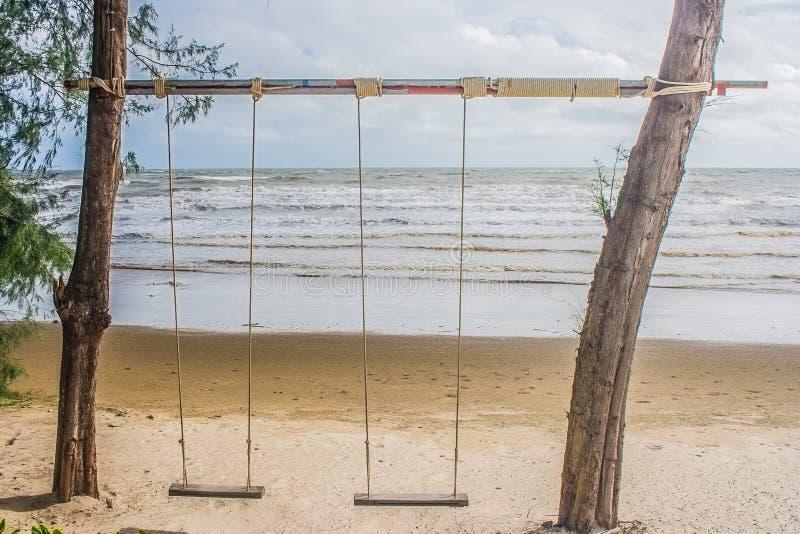 垂悬从在海滩的树的木摇摆有海景视图背景 免版税库存照片
