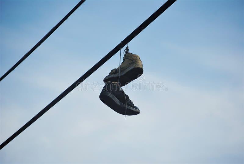 垂悬从电话电汇的运动鞋 免版税图库摄影