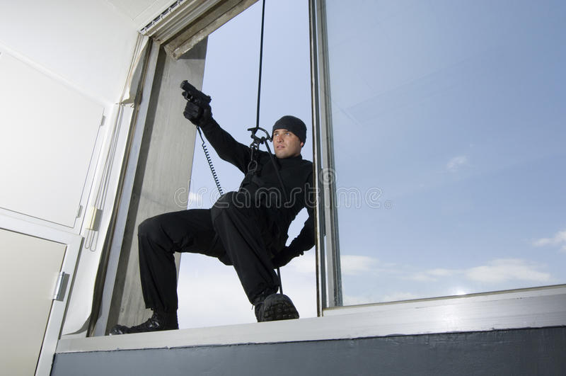 垂悬从窗口的特警队官员 图库摄影