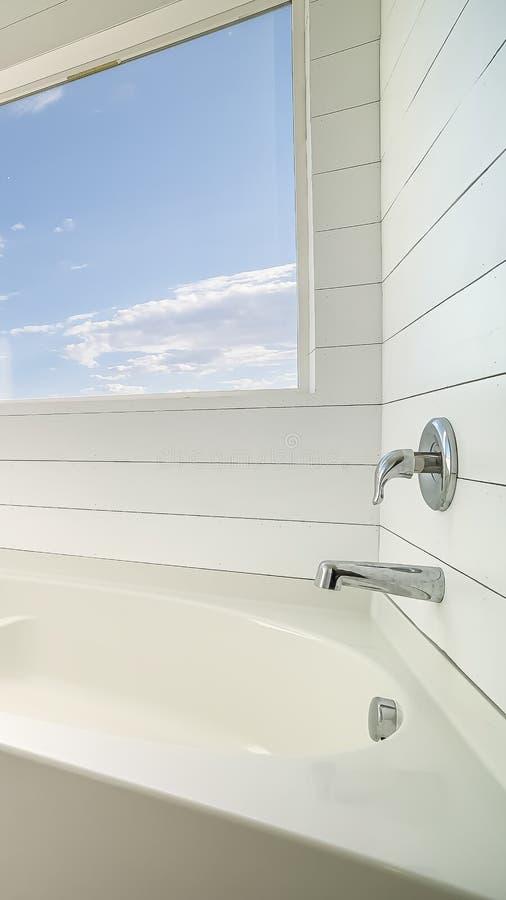 垂直的最低纲领派与白色浴缸和白色墙壁的卫生间室内设计 库存照片