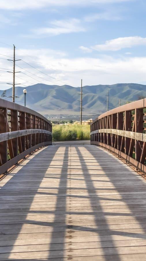垂直的有金属格子栏杆的框架木桥在一个湖有山看法  库存图片