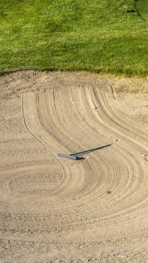 垂直的框架关闭高尔夫球场与犁耙创造的一个圆样式的沙子地堡 库存照片