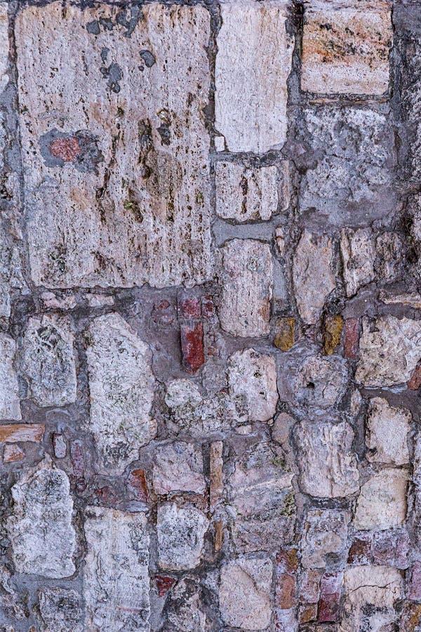 垂直的石床钙质块许多鹅卵石米黄参差不齐的被风化的老基本的设计系列  库存照片