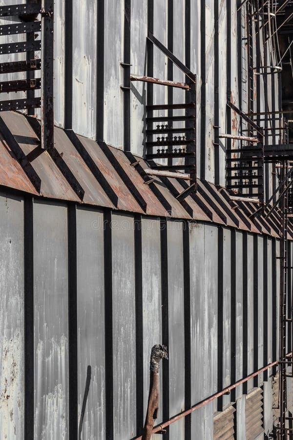 垂直的金属盘区对高墙壁,透视图 库存图片