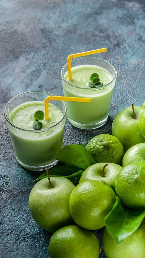 垂直的食物横幅圆滑的人苹果和石灰在深蓝具体背景 戒毒所programm 免版税库存照片
