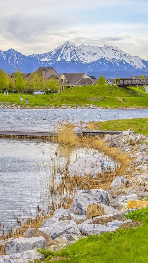 垂直的高一个风景湖的框架木甲板有岩石的和在岸的鲜绿色的草 库存图片