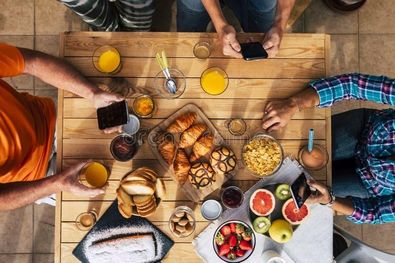 垂直顶端视野中的早餐时间与朋友一起吃-科技移动互联网社交网络成瘾 库存图片