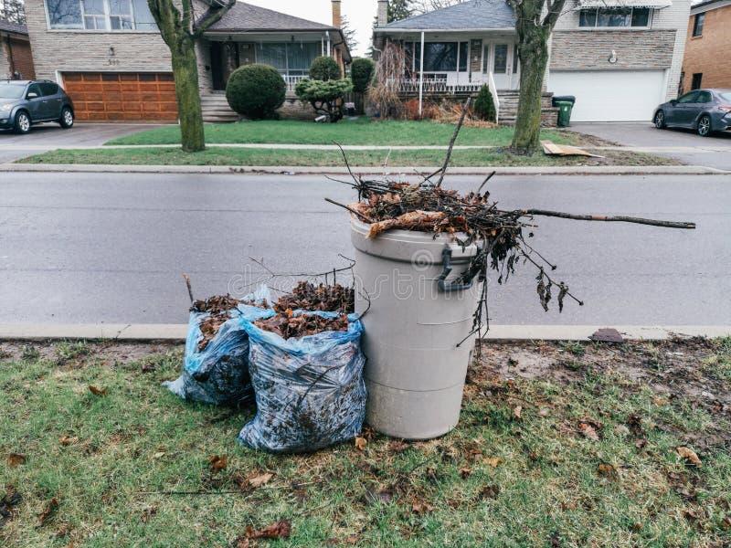 垃圾废垃圾桶和塑料袋有被切开的老树枝干燥秋叶的在街道上在住宅区 免版税库存图片