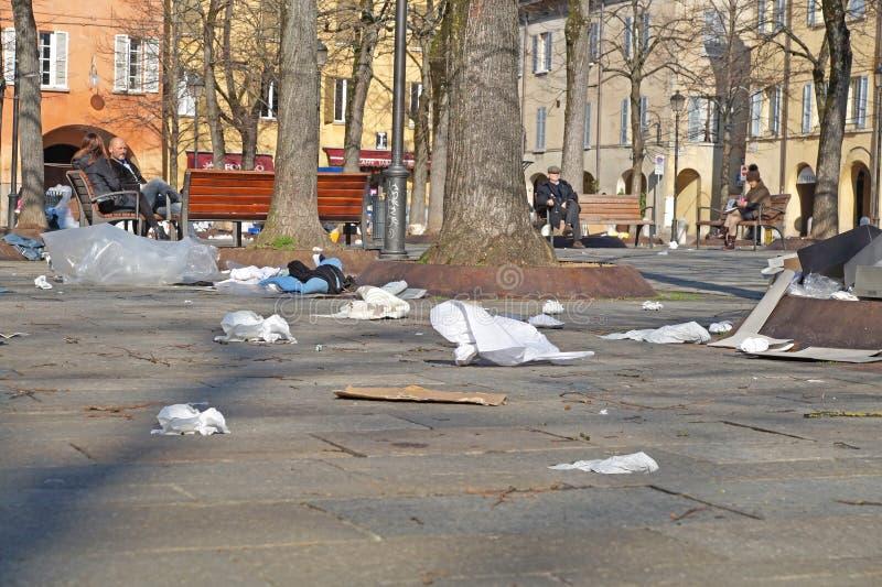 垃圾箱 自行车前轮离地平衡特技容器 垃圾袋 垃圾驱散了在郊区街道上的路 回收废物处置 免版税图库摄影