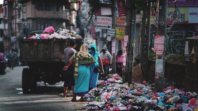 垃圾车投下垃圾和垃圾在Thamel街上 免版税库存照片