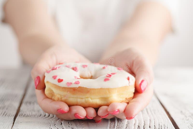 垃圾食品和吃光概念-接近拿着上釉圆环的女性手 免版税库存照片