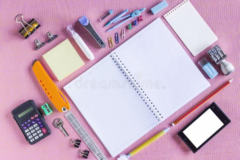 类型组织的五颜六色的学校用品在笔记本附近开放对被安排的空白页 免版税库存图片