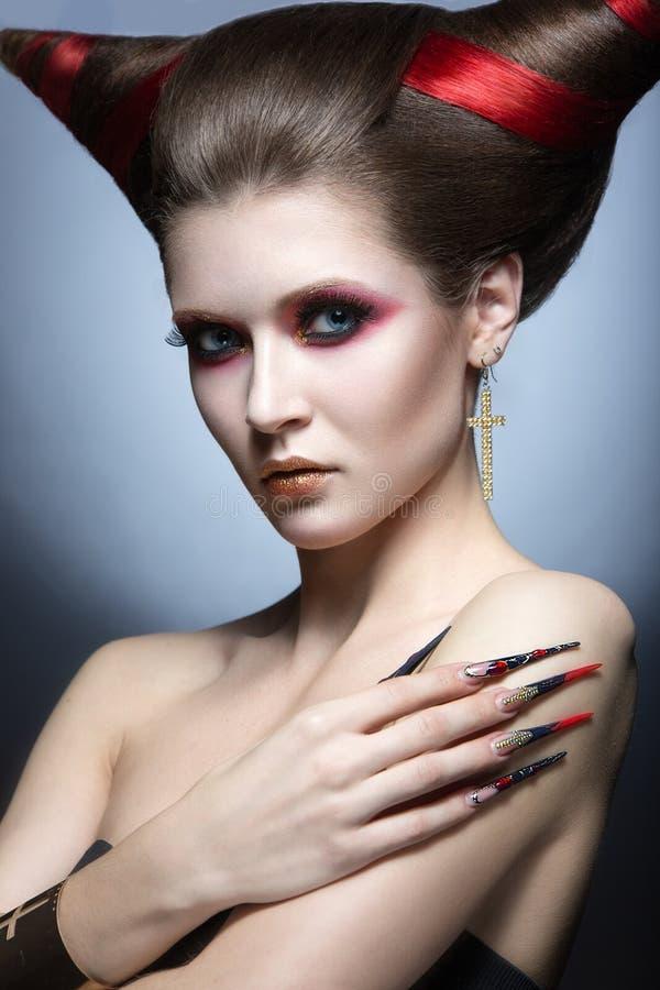 以垫铁的形式邪魔诱惑者和理发的图象的女孩有长的钉子的 图库摄影