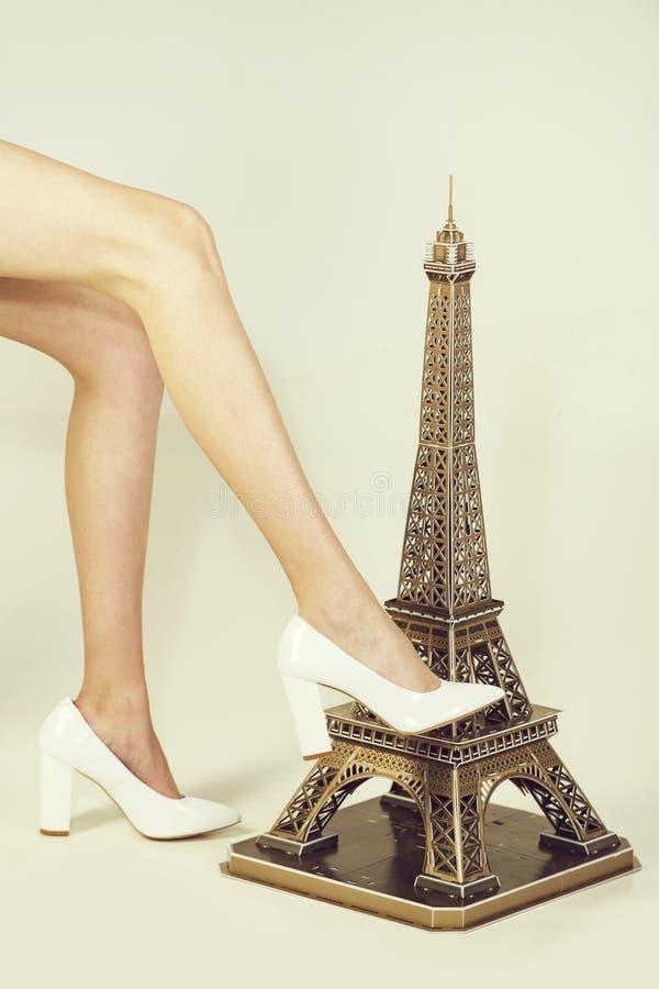 埃佛尔铁塔在白色背景的演播室 妇女模型的美好的长的腿在小的埃佛尔铁塔附近的 免版税库存照片