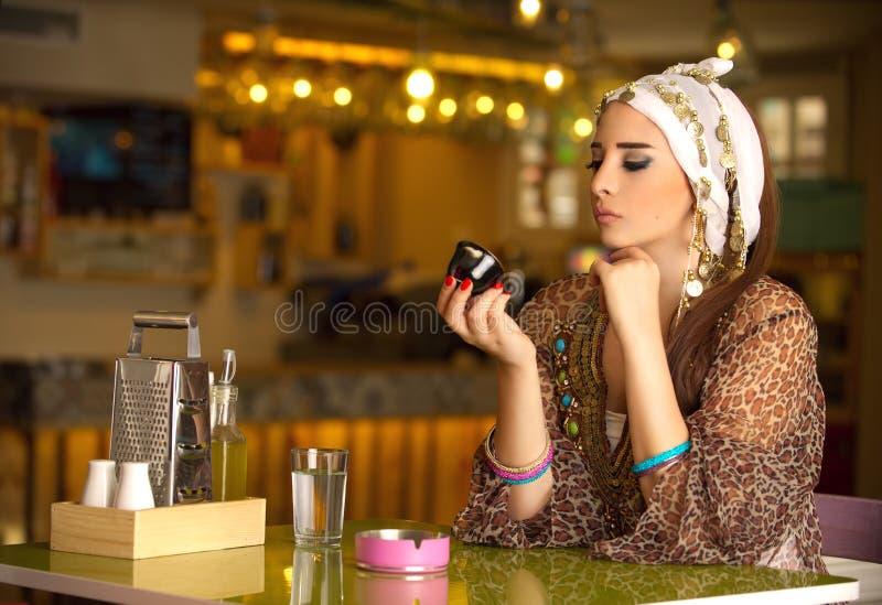 埃及美丽的妇女饮用的咖啡 免版税库存图片