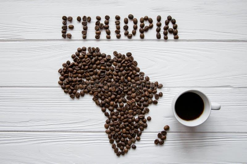 埃塞俄比亚的地图放置在与咖啡杯的白色木织地不很细背景的由烤咖啡豆制成 库存图片