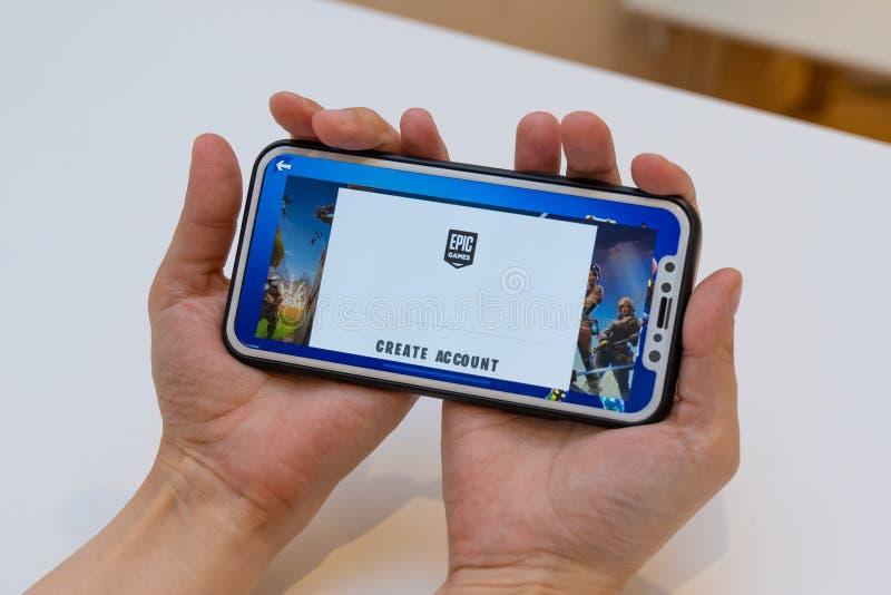 埃尔瓦,爱沙尼亚- 2018年11月15日:女孩与网上Fortnite比赛史诗比赛商标的藏品iphone和创造帐户词 图库摄影