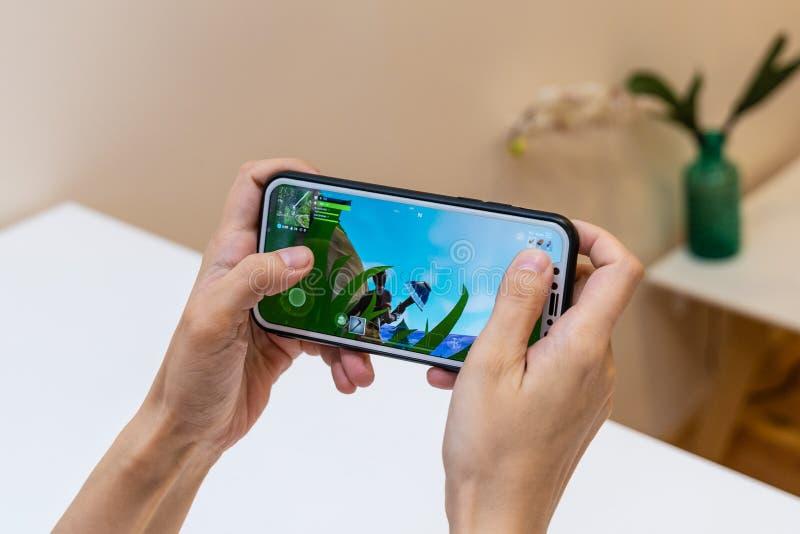 埃尔瓦,爱沙尼亚- 2018年11月15日:女孩与网上Fortnite比赛的藏品iphone在显示,打电子游戏 免版税库存图片