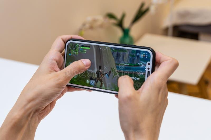 埃尔瓦,爱沙尼亚- 2018年11月15日:女孩与网上Fortnite比赛的藏品iphone在显示,打电子游戏 免版税库存照片