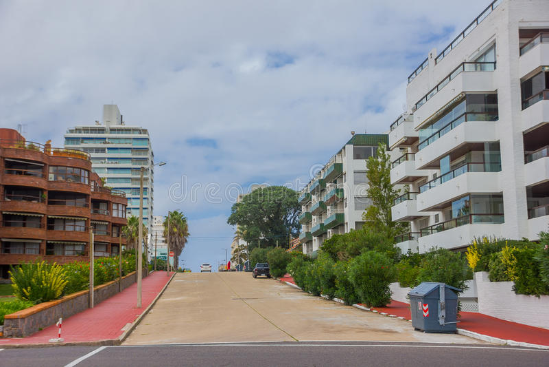 埃斯特角城,乌拉圭- 2016年5月06日:有红砖的一点街道在人行道、现代大厦和多云天空作为backgr 免版税库存照片