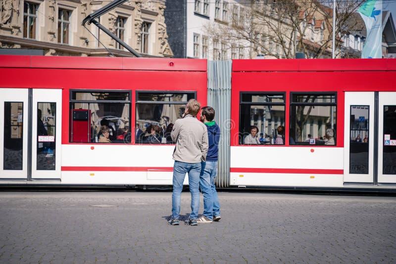 埃福特,德国 2019年4月7日 两偶然年轻人在红色电车背景的市中心 免版税库存图片