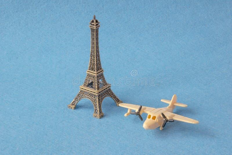 埃菲尔山与一点玩具飞机的塔模型在蓝色背景 著名法国地标和飞机缩样,巴黎 库存照片