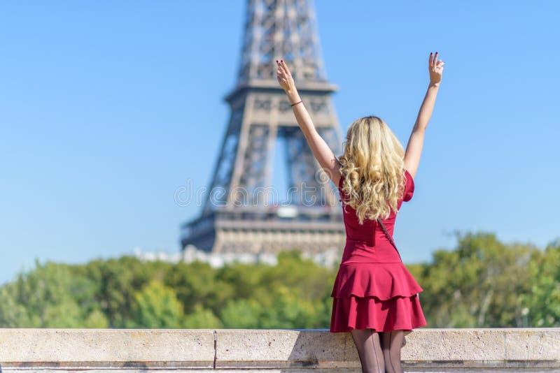 埃菲尔铁塔的妇女 一件红色伯根地浪漫礼服的年轻旅游女孩敬佩看法的 画象软的bokeh 免版税图库摄影