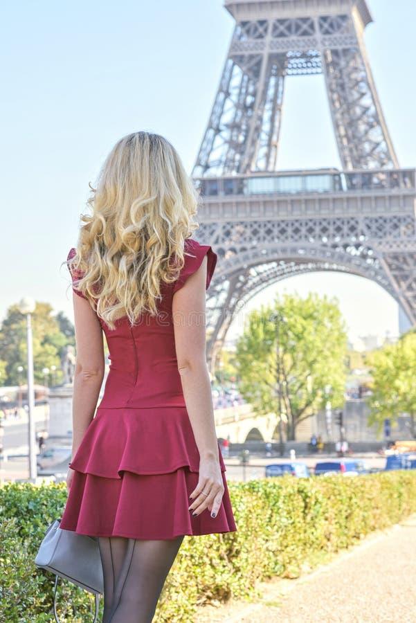 埃菲尔铁塔的巴黎,法国妇女 一件红色伯根地浪漫礼服的年轻旅游女孩敬佩看法的 画象 库存图片