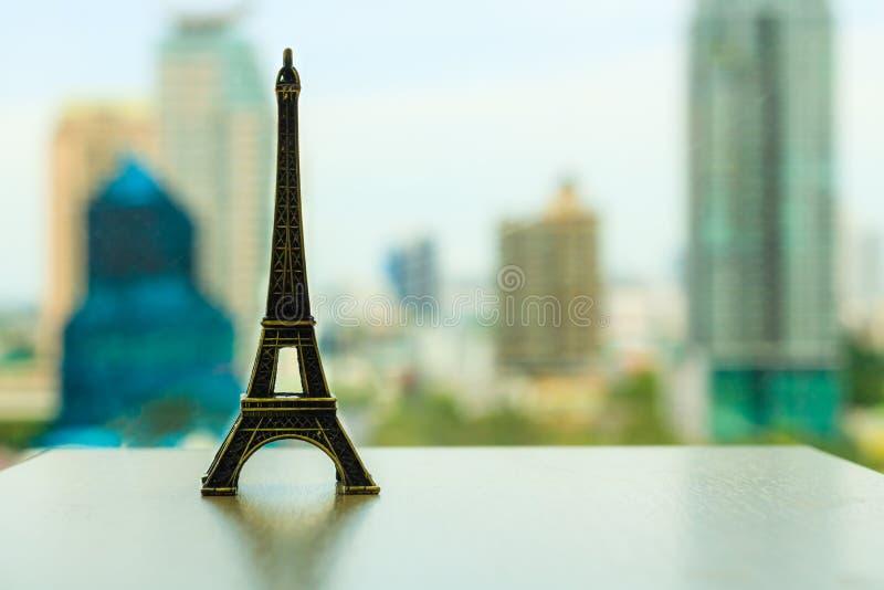 埃菲尔铁塔的模型在一张桌上的在t的都市风景场面后 免版税库存图片