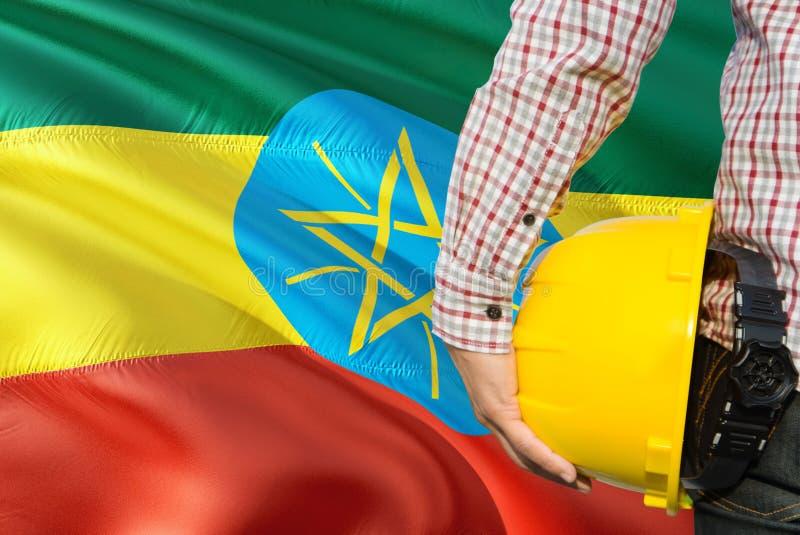 埃赛俄比亚的工程师拿着与挥动埃塞俄比亚旗子背景的黄色安全帽 建筑和大厦概念 免版税库存照片