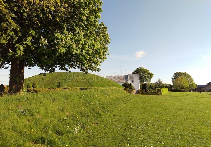埋葬土墩和教会具体化的,丹麦 库存照片