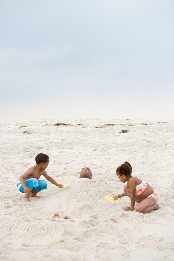 埋葬父亲的孩子在沙子 免版税库存图片