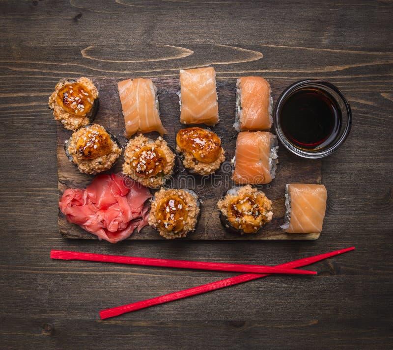 费城与三文鱼和被烘烤的寿司的寿司卷与螃蟹用姜和酱油红色筷子在木土气backgr 库存照片
