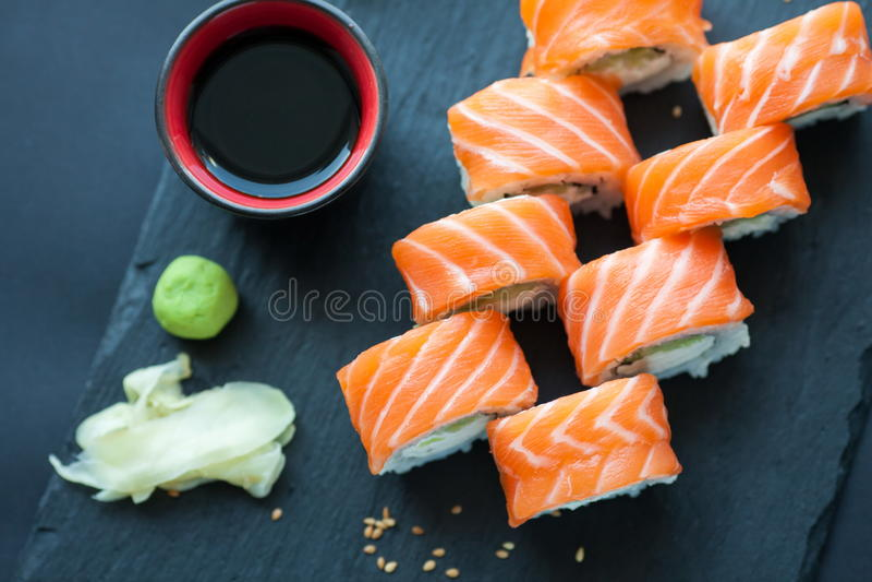 费城在黑暗的石背景的卷经典之作 费城乳酪,黄瓜,鲕梨 日本寿司 顶视图 免版税图库摄影