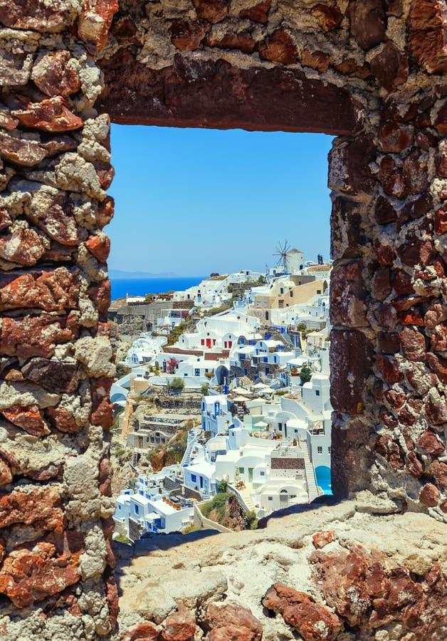 城堡窗口有破火山口和古典教会有蓝色圆顶的, Oia,圣托里尼,希腊看法  库存照片