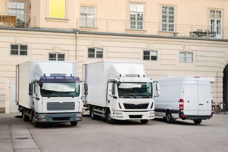 另外中小型的递送急件服务卡车和搬运车在大厦庭院 城市交付货物送货公司 免版税图库摄影