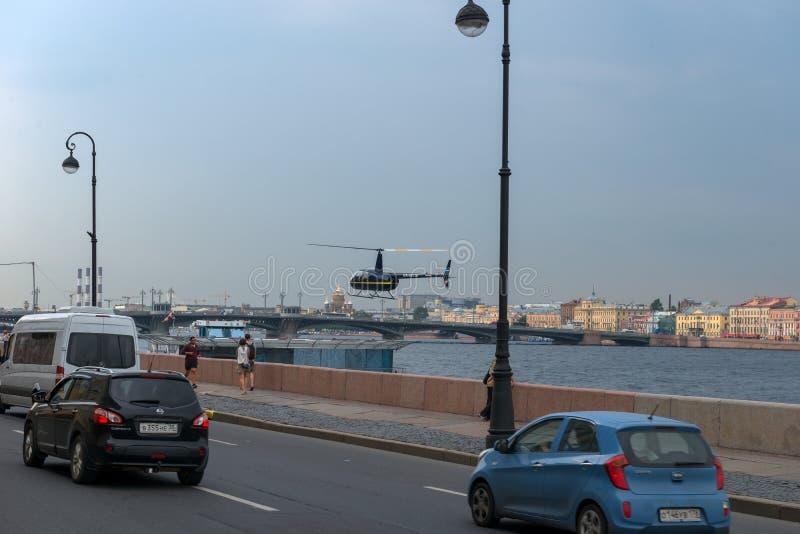 城市交通和登陆在一个浮动平台的一架直升机在涅瓦河 免版税图库摄影