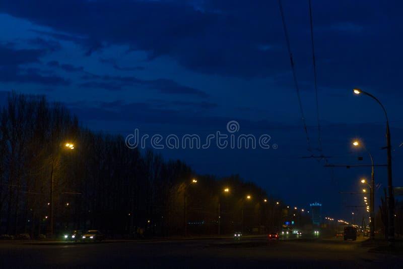 城市光芒的夜城市点燃与路、汽车、电缆和树 免版税库存图片