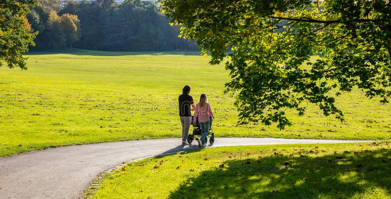 城市公园,慕尼黑,德国 一年轻加上的看法走在道路的婴孩推车 免版税库存图片