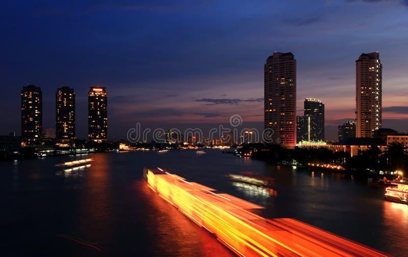 城市和夜间的河。 免版税库存图片