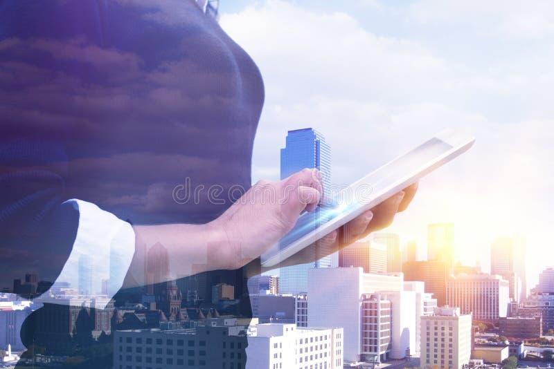 城市和女商人手两次曝光使用数字式片剂 图库摄影
