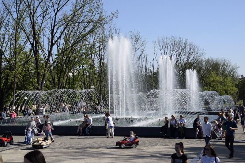 城市喷泉在市克拉斯诺达尔 人们由喷泉走 3d背景回报飞溅空白的水 免版税库存照片