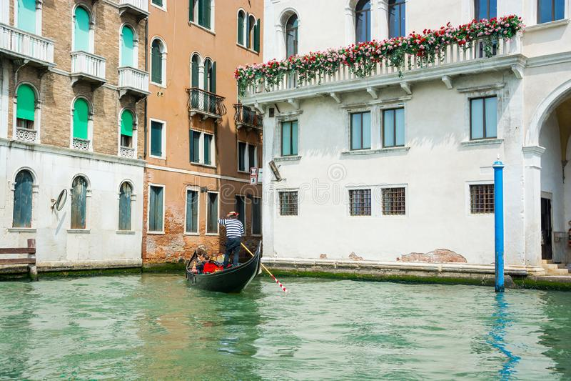 城市大运河的看法在威尼斯在一好日子 驾驶长平底船的平底船的船夫在威尼斯,意大利 库存图片