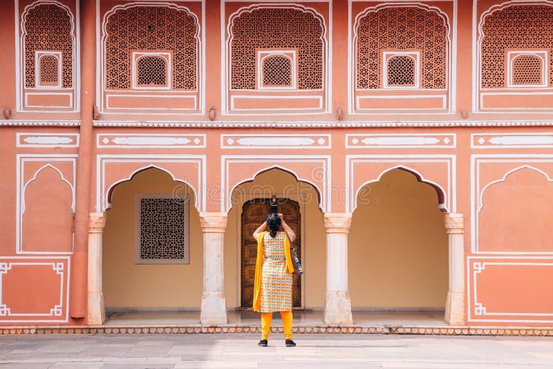 城市宫殿、桃红色墙壁和妇女在斋浦尔,印度 图库摄影