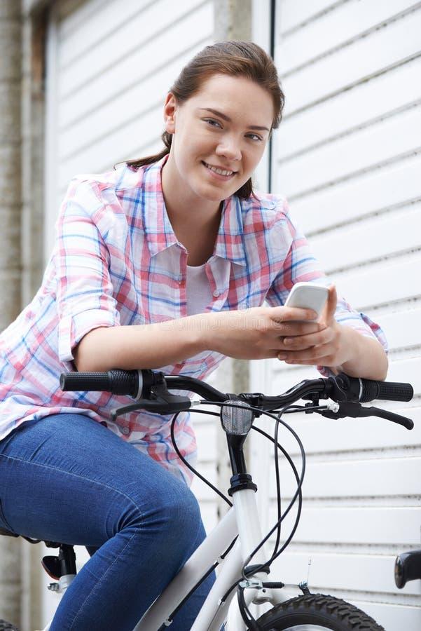 城市布局的十几岁的女孩使用手机,乘坐B 免版税库存照片