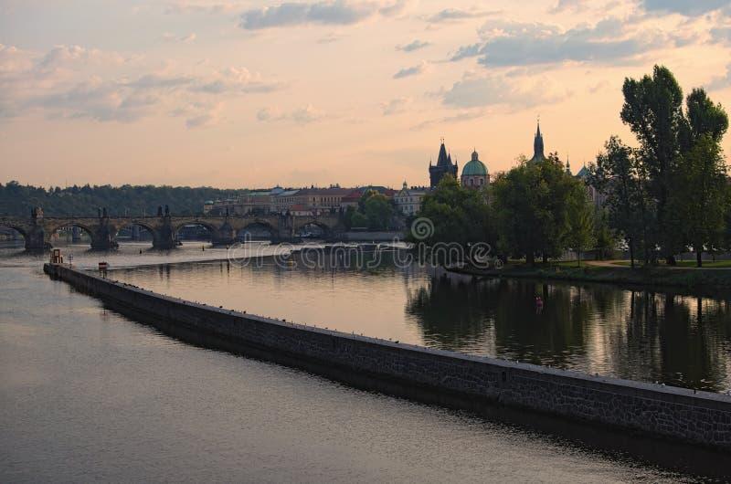 城市布拉格的美丽如画的看法在早晨 在伏尔塔瓦河河和阿切尔` s的查理大桥海岛 免版税库存照片